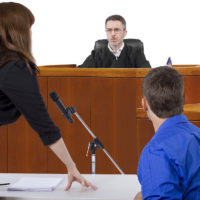 divorce lawyer talking to judge in courtroom with defendant present
