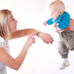 father hands child to mother pointing out parenting time pointing at watch