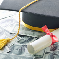 college graduation hat with diploma on top of pile of money
