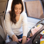 Young mom securing child rear-facing car seat