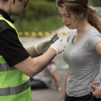 Police administering breathalyzer test to woman