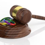 Gavel and gay marriage rings on white background