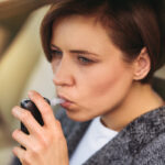 Woman using breath alcohol analyzer in the car