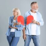 Mature couple with torn paper heart on grey background. Relationship problems